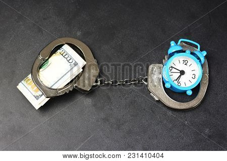 Handcuffs, Money And Alarm Clock On Dark Background, Bail Concept