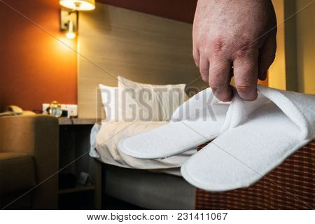 Hands Hold White Slippers In The Hotel Room Or In The House Room