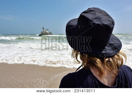 Lonely Woman Standing On The Beach Looking At The Sinking Ship From Shipwreck. Atlantic Coast In Nam