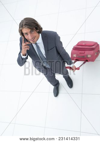 businessman with travel suitcase talking on the phone.