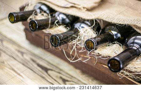 Empty Wine Bottles In A Wooden Box On A Rustic Table. Background