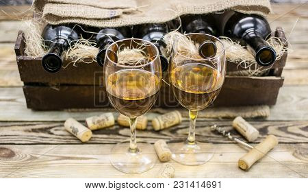Two Glasses Of White Wine On A Wooden Background.