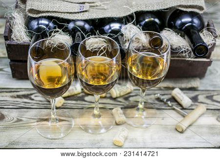 Three Glasses Of White Wine On A Wooden Background. Alcoholic Beverages Background