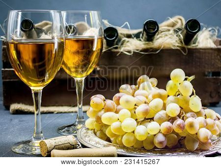 White Dry Wine. Two Glasses Of Wine Against A Dark Background. Alcoholic Beverages Background. House