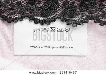 Composition And Care Clothes Label On Pink Textile Background With Black Lace