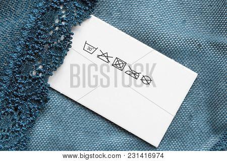 Care Clothes Label On Blue Textile Net Background Closeup