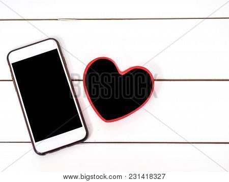 Mobile Phone On White Chair Background With Small Board Heart , Black Space For Insert Text Or Image
