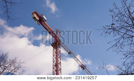 Construction Tower Crane Against Blue Sky And White Clouds