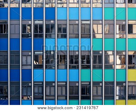 Facade Of A Modern Skyscraper With Colored Panals And Glass Windows In The Commercial District Of A