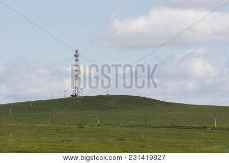 Telecommunication Tower On A Field At Summer Day