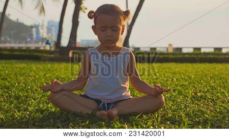 Little Cute Girl Meditates In Turkish Pose On Lawn In A Park At Sunset.