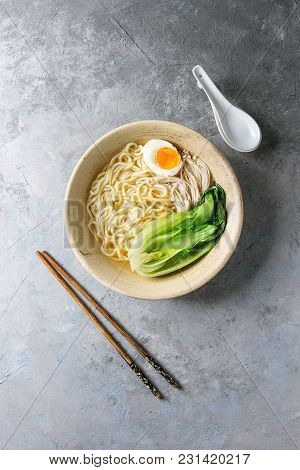 Asian Dish Udon Noodles With Boiled Egg, Mushrooms, Boc Choy Served In Ceramic Bowl With Spoon And C