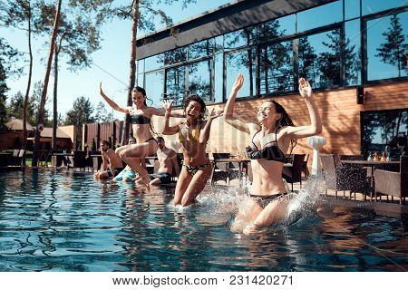 Joyful Young Girls In Swimsuits Jumping Into Pool. Friends Carefree Spend Time Near Water. Guys And