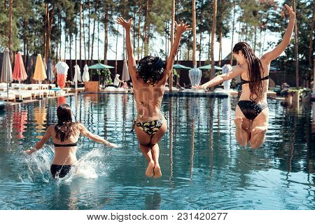 Joyful Young Girls In Swimsuits Jumping Into Pool. Friends Carefree Spend Time Near Water. Beautiful