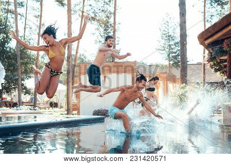 Company Of Happy Young People Jumping In Pools Forming Splashes. Swimming Pool Party Concept. Holida