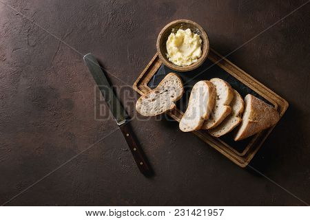 poster of Loaf of fresh baked sliced artisan baguette bread with butter and vintage knife on wooden slate serving board over dark brown texture background. Top view, copy space.