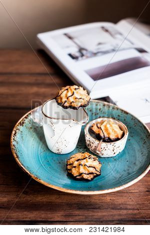Coconut Macaroon Cookies Dipped In Dark Chocolate On A Plate On A Wooden Table, Selective Focus. Ima