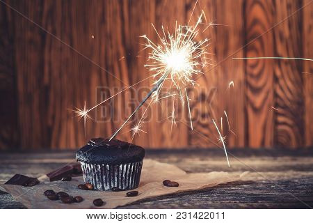 Chocolate Cupcake With A Sparkler On Wooden Background.