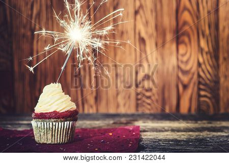 Cupcake With Cream Cheese, With Sparkler On Dark Wooden Background.