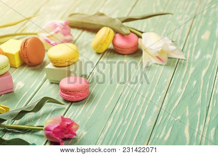 Beautiful Tulips With Colorful Macaroons On Greenery Wooden Background. Copy Space. Selective Focus.