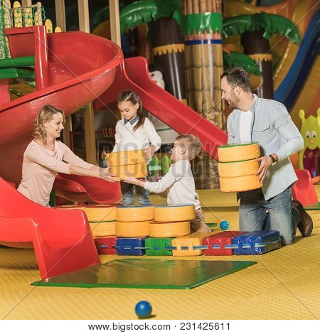 Happy Family With Two Little Kids Playing Together In Entertainment Center