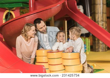 Happy Parents Looking At Adorable Little Kids Playing Together In Game Center