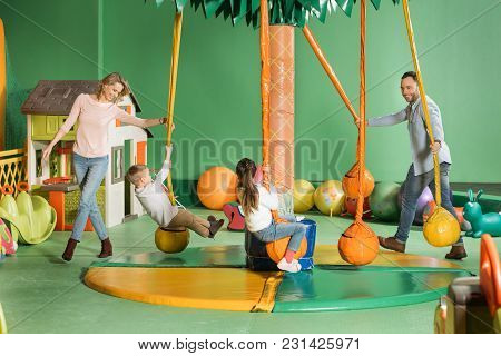Smiling Parents Looking At Happy Children Swinging On Swings In Entertainment Center