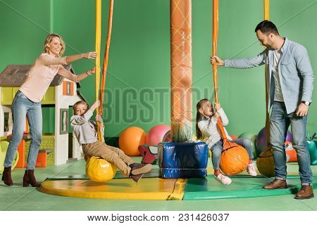 Happy Parents Looking At Kids Swinging On Swings In Entertainment Center