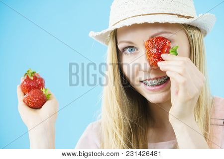 Young Positive Woman Playing With Fresh Strawberries Fruits, On Blue. Healthy Meal.