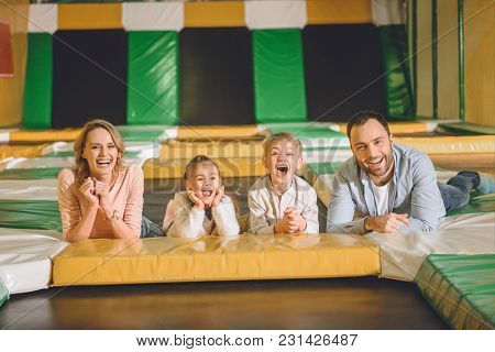 Happy Family Laughing And Smiling At Camera While Lying Together At Indoor Play Center