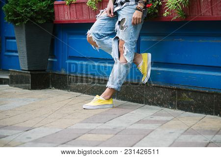 Female Legs In Bright Yellow Sneakers And Jeans On The Tile Of The City Square. Street Photography