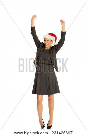 Happy businesswoman wearing christmas hat.