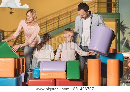 Happy Parents With Daughter And Son Playing Together With Colorful Blocks In Entertainment Center