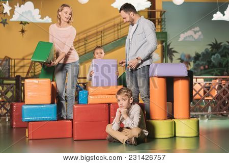 Bored Little Boy Sitting On Floor While Happy Family Playing With Blocks In Entertainment Center