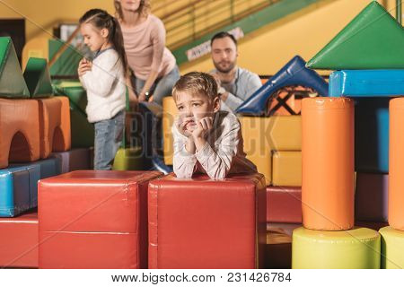 Bored Little Boy Looking Away While Family Playing With Colorful Blocks In Entertainment Center