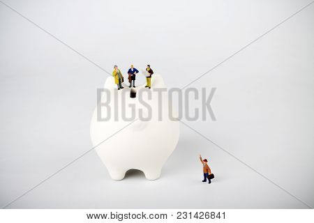 Businessman Figurines On A Piggybank. Money, Business, Corruption And Expectation Concept.