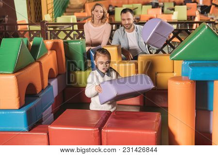 Happy Parents Looking At Little Daughter Building Castle With Colorful Blocks In Game Center