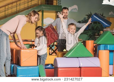 Happy Family With Two Kids Building Castle With Colorful Blocks At Entertainment Center