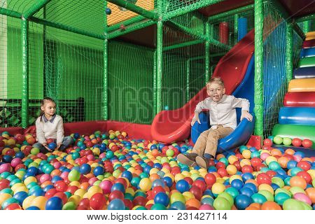 Happy Siblings Playing In Pool With Colorful Balls At Entertainment Center