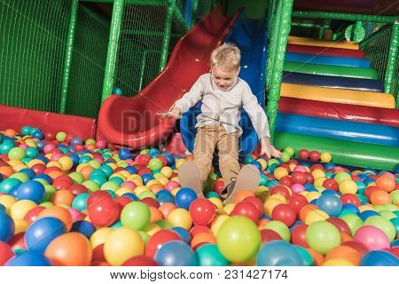 Cute Happy Little Boy Playing In Pool With Colorful Balls