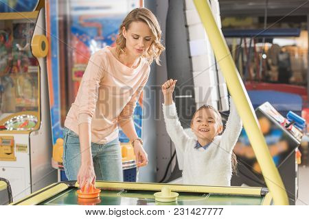 Smiling Mother And Triumphing Little Daughter Playing Air Hockey In Game Center