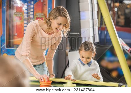 Selective Focus Of Happy Mother And Daughter Playing Air Hockey In Entertainment Center