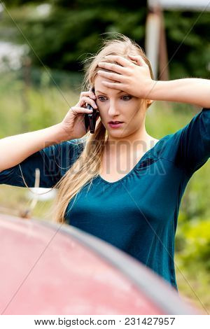 Woman dialing her phone after car accident.