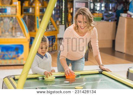 Happy Mother And Daughter Playing Air Hockey Together In Entertainment Center