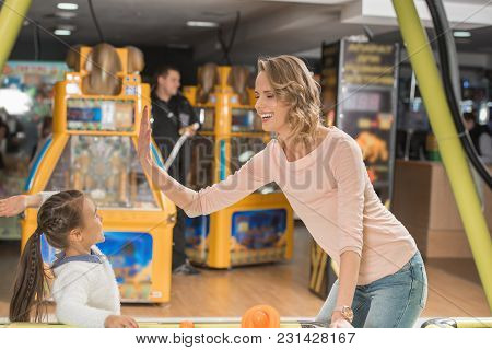 Happy Mother And Daughter Giving High Five While Playing Air Hockey Together