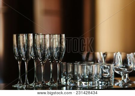 Glasses For Champagne Stand On The Table In Front Of The Buffet