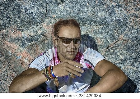 An Athletic Charismatic Man With A Harsh Look Sits With His Back To The Rock And Smokes. He Is A Mou