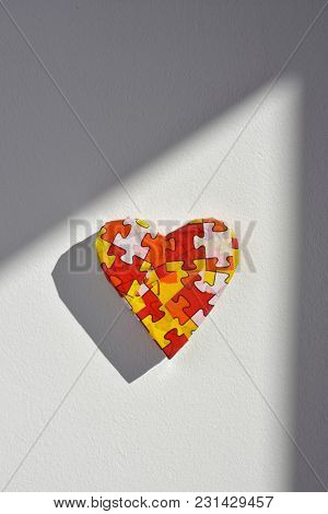 a heart patterned with many puzzle pieces of different colors, symbol of the autism awareness, on a white background