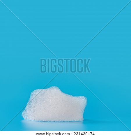 White Soap Bubbles Foam On Blue Background. Suds Shower Texture Macro View Photo, Shallow Depth Of F