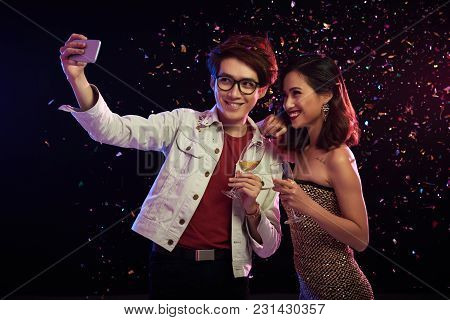 Loving Asian Couple With Champagne Flutes In Hands Talking Selfie On Smartphone While Celebrating Mo